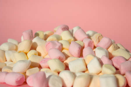 Marshmallows on pink background with copyspace. Flat lay or top view with boke on background