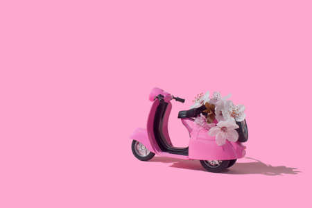 Pink retro toy car delivering bouquet of flowers box on pink background. February 14 card, Valentine's day. Flower delivery. 8 March, International Happy Women's Day. Mother's day.