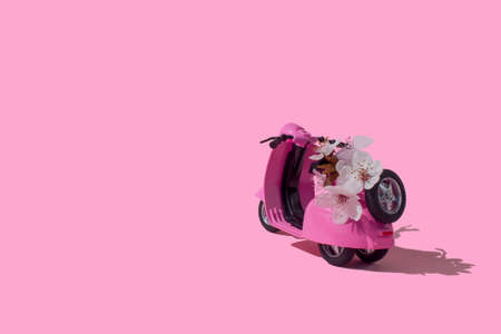 Pink retro toy car delivering bouquet of flowers box on pink background. February 14 card, Valentines day. Flower delivery. 8 March, International Happy Womens Day. Mothers day.