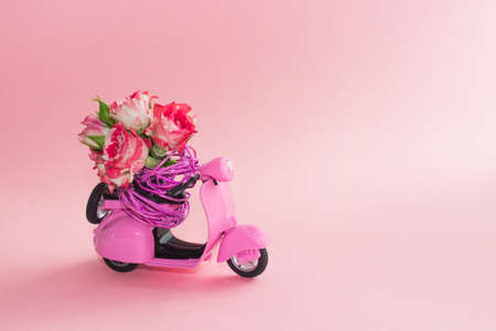 bouquet of roses in basket on backseat of cute pink scooter on pink background. Flower delivery.