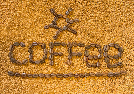 the word coffee from the coffee beans on the background of scattered instant coffee