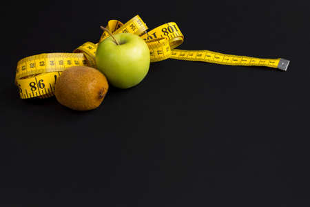 Green apple, kiwi and measuring tape  with centimeters and inches isolated on black background. Stok Fotoğraf