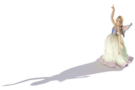 porcelain figurine of a dancer in a dress with wings and shadow isolated