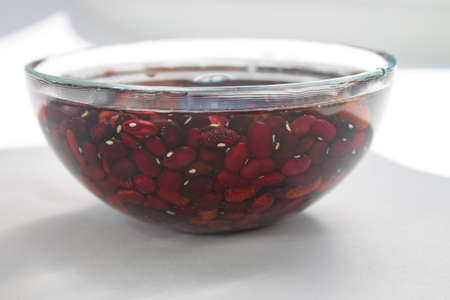 lots of raw red bean beans soaked in water in a clear glass bowl on a white table with sun shade.