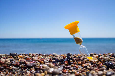 yellow hourglass with crumbling sand stands with slope on the wet sea pebbles with the sea and the clear sky in the background Imagens