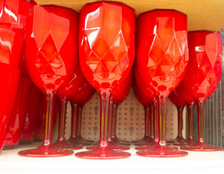 Many red wine glasses with geometric form on the shelve in the store.
