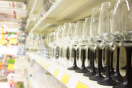 Many wineglasses with black footing on the shalve in the store with space for prices. Stock Photo