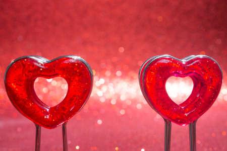 Two red hearts on a stand in the foreground on a red background with bokeh. Stock Photo