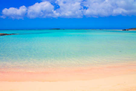 Beach with pink sand and turquoise water and clouds in blue sky. Wallpaper or background. Tropical view.