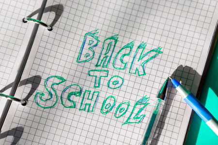 It's time to go back to school. Lettering in a notebook in a cage with colored pens. Green and blue paste. Longing for school days.
