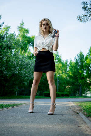 A teenage girl in a black skirt and white blouse. Light, elegant hair. Sunglasses. It stands in a Park on an asphalt path.