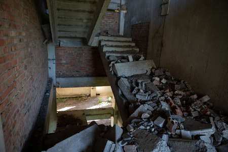 A ruined, crumbling staircase in an abandoned building. A flight of stairs collapsed in the entrance of an unfinished house