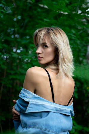 The girl with the denim jacket pulled down bared her shoulders. A woman against a background of green trees stands with her back to the camera. Reklamní fotografie