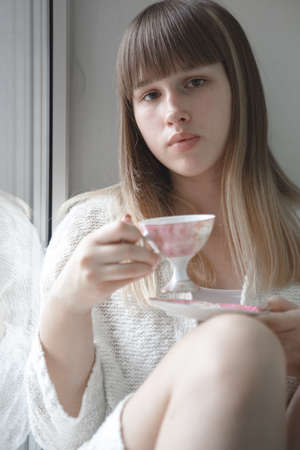 A teenage girl with blond hair in a white knitted Cape is drinking tea sitting on the window sill