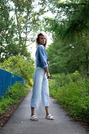 a girl with blond hair on an asphalt path along a fence and trees. The girl in full growth ties a blue denim jacket. Reklamní fotografie
