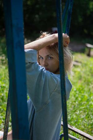 Blonde girl on a swing. A girl with blond hair, a denim blue suit, is sitting on a swing in a garden among green plants. Reklamní fotografie