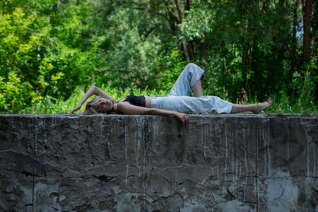 A girl in a black top and blue jeans is lying on a concrete fence with a vintage texture. A woman with light hair enjoys lying on the street