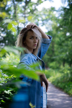 A girl with blond hair and a blue denim jacket is leaning against a blue fence.