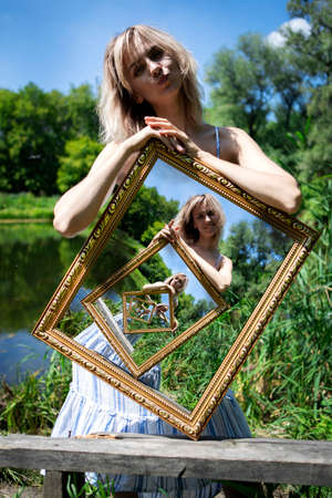 Optical illusion. The composition of an infinite image in a picture. A girl with blond hair on the lake shore holds a picture with an infinite image. A picture within a picture.