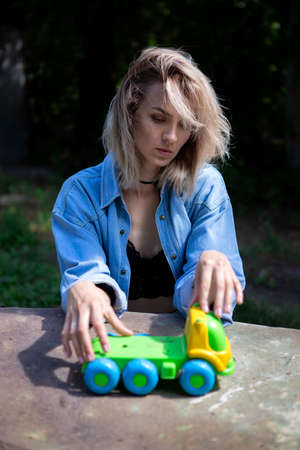 A girl in a denim suit sits on a bench at a table outside in the garden and rolls a small toy car. Adult childhood memories, boredom