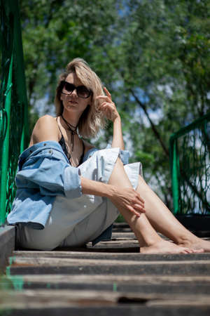 A girl with blond hair and sunglasses is sitting on the stairs leaning on the railing. A woman in a denim suit and bare feet in the sun Reklamní fotografie