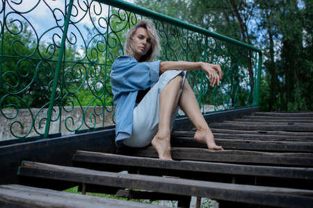 a blonde girl is sitting on the steps of a staircase with a fence. A girl in a denim suit with bare feet.