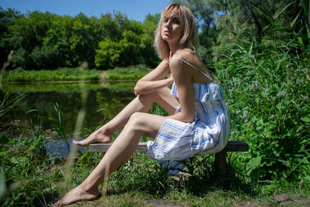 A girl in a dress on the shore of a lake sits on an old bench on a Sunny day. Girl with light hair by the water in nature