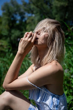 portrait of a girl with light hair in nature. Blonde face hair style. Close his eyes. Sunlight.