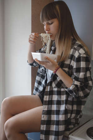 A teenage girl with blond hair, in a plaid shirt on. The girl is eating instant noodles in a disposable dish and a plastic fork.