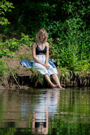 A girl with blond hair on the lake shore has her feet in the water and is swinging them creating a spray of water. Girl in a denim suit in nature