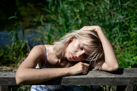 The girl with the blond hair on the lake shore rested her elbows and head on the bench. A thoughtful woman in a dress. Rest, relaxation, recuperation.