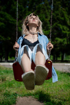 a woman swings on a swing stretching her legs. A blonde girl in a denim suit recalls her childhood Reklamní fotografie