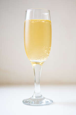 A glass of white sparkling wine. Champagne on the white table. Drink close-up. Gas bubbles in an alcoholic drink.