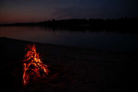 Bonfire on the river Bank at night. Red flames from burning branches and firewood near the reservoir in summer. Outdoor recreation by the fire.