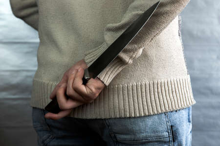 An evil man holds a knife behind his back, waiting for the victim. A maniac and a rapist with a gun.