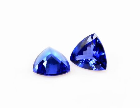 Pair of trillant shape tanzanite gemstones, isolated over white.