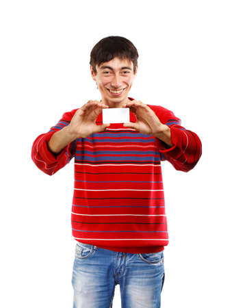 Smiling man in red striped sweater on white background with business card photo