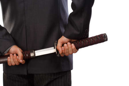Man in business suit holding half pulled katana sword behind back isolated on white background