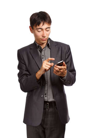 Young businessman in dark grey suit stands with mobile phone isolated on white background photo