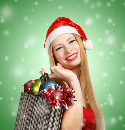 Beautiful young woman in santa claus suit holding box with christmas and new year attributes and gifts on green background with falling snowflakes photo