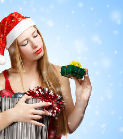 Beautiful young woman in santa claus suit holding box with christmas and new year attributes and little gift box on blue background with falling snowflakes photo