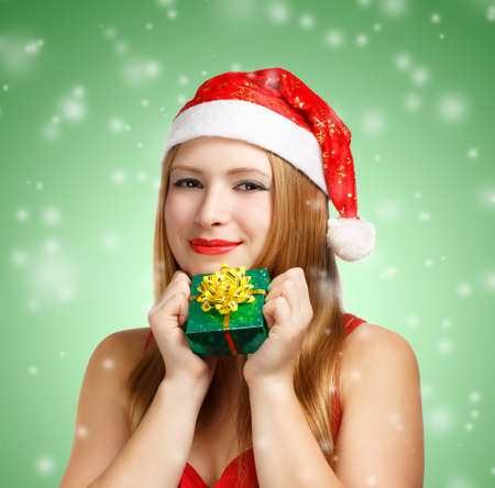 Beautiful young woman in santa claus suit with little gift box on green background with falling snowflakes photo