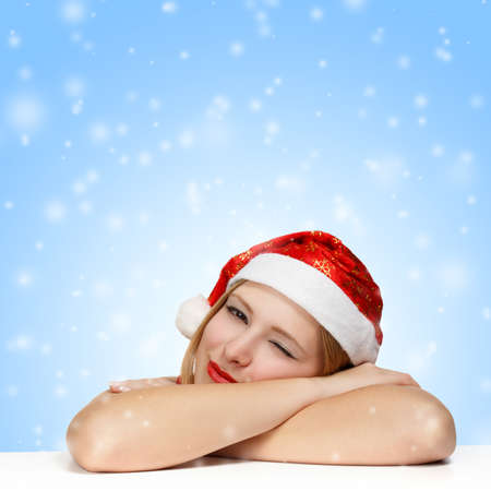 Sleepy beautiful young woman in santa claus hat laying on the table on blue background with falling snowflakes photo