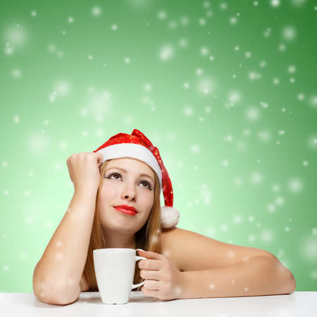 Beautiful young woman in santa claus hat siting at the table with white cup on green background with falling snowflakes photo