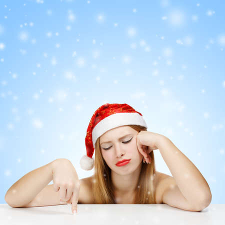 wearied: Young woman in santa claus hat posing with wearied look on blue background with falling snow Stock Photo