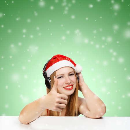 Young woman in santa claus hat and headphones with thumbs up gesture on green background with falling snow photo