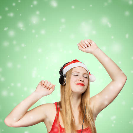 Young woman in santa claus hat and headphones take pleasure from music on green background with snowfall photo