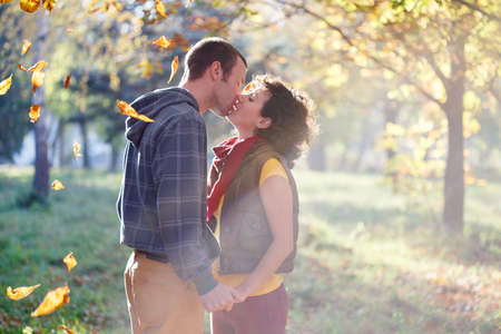 Loving couple kissing in the park in the sunlight on trees background photo