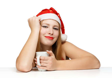 Beautiful young woman in santa claus hat sitting at the table with white cup on white background photo