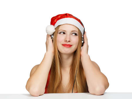Young woman in santa claus hat and headphones isolated on white background Stock Photo